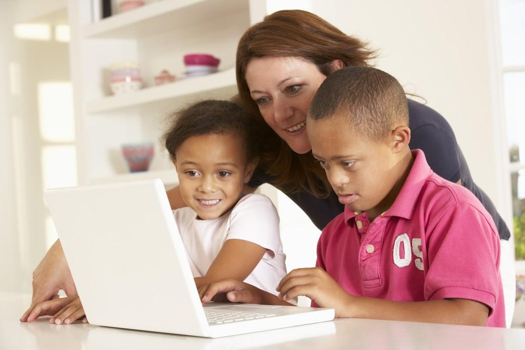 woman teaching two kids